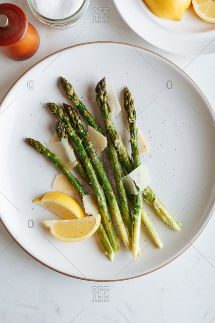 Baked parmesan asparagus laid out on a white plate with lemon wedges served nearby.