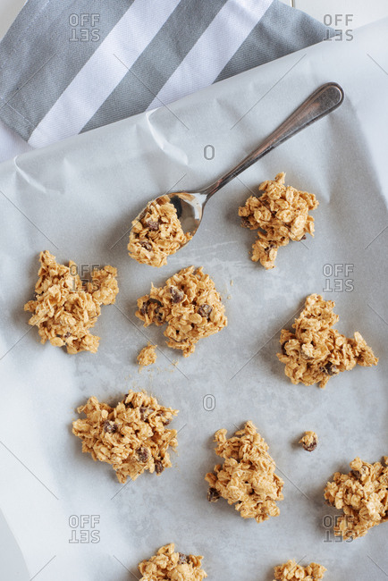 Gluten free batter of chick pea flour made into oatmeal chocolate chip cookies arranged on a baking sheet with a spoon for sizing nearby.