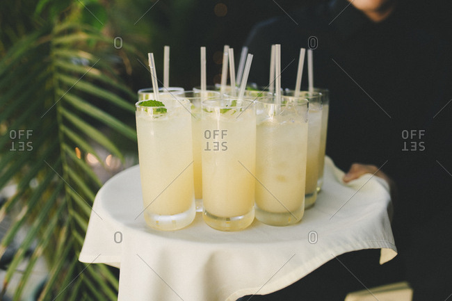 Server carrying tray filled with cocktails