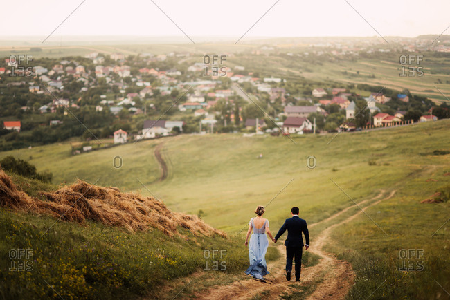 Bride and groom walking down a hill hand in hand