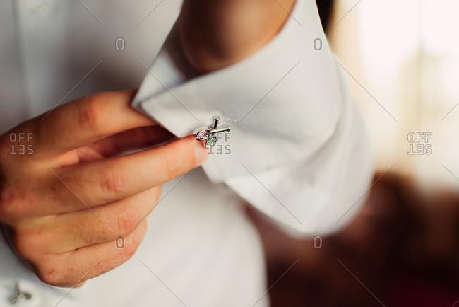 Groom buttoning tennis racquet cufflinks on his shirt