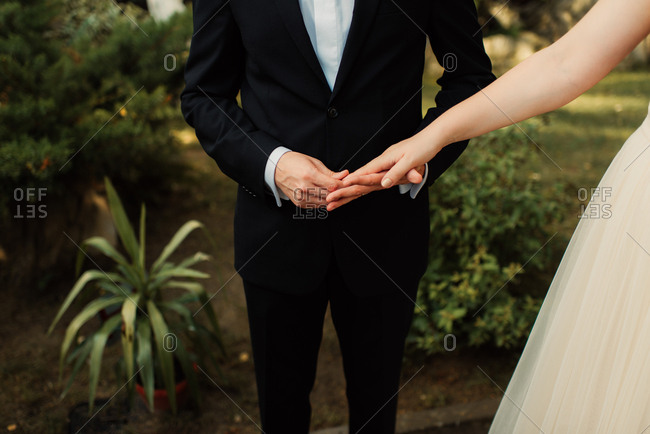 Groom holding his bride's hand