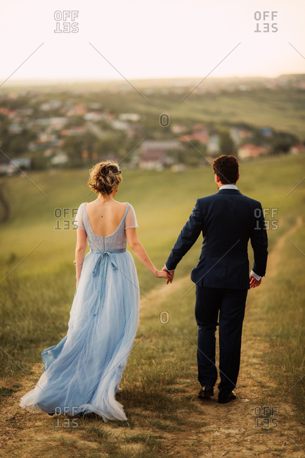 Bride and groom walking on a path hand in hand