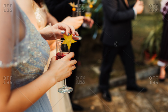Wedding guest drinking cocktail garnished with starfruit