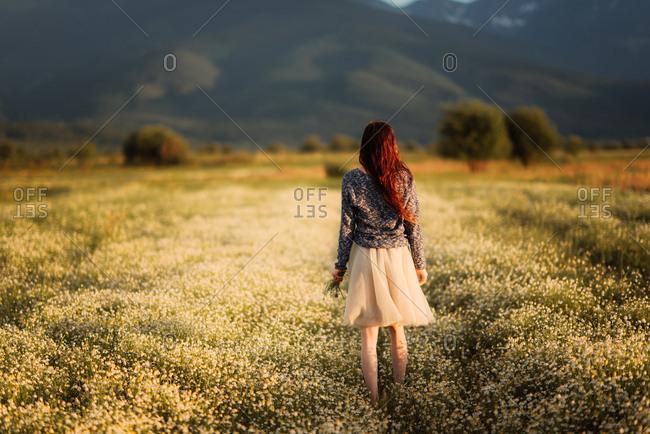 Redhead woman walking through rural field