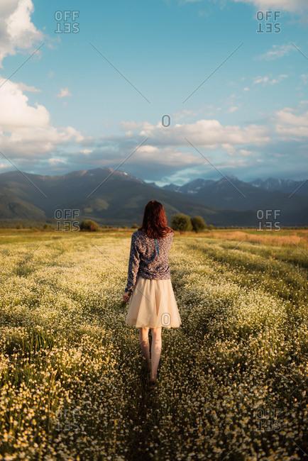 Redhead woman walking through mountainside field
