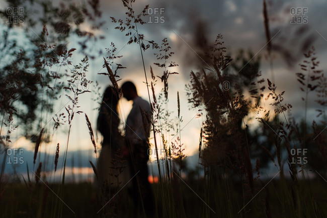 Silhouette of couple embraced in the country at sunset