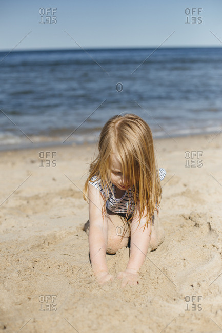 Girl digs in sand at shore