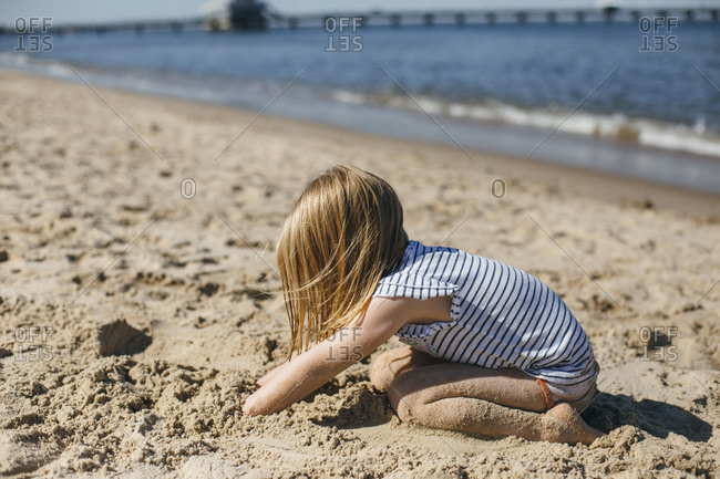 Girl buries her hands deep into sand