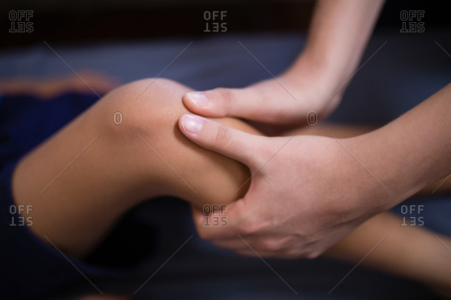 Close-up of female therapist massaging knee at hospital ward