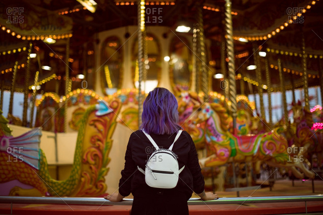 Rear view of woman standing in amusement park at night
