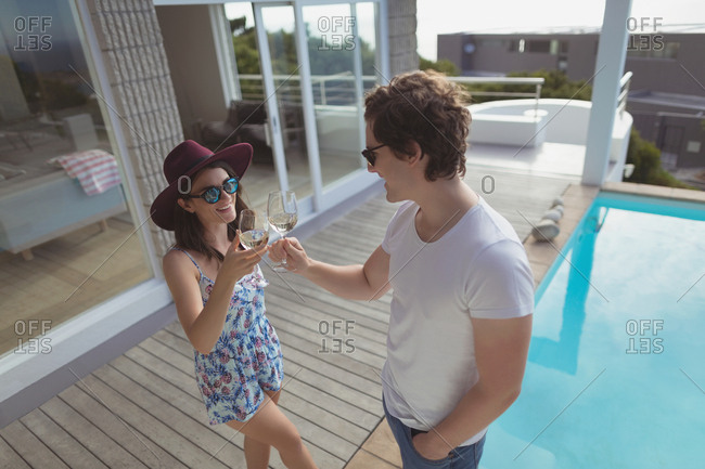 Couple toasting glasses of wine near pool side at home