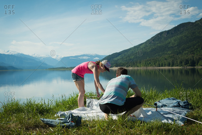 Couple putting up a tent in countryside on a sunny day