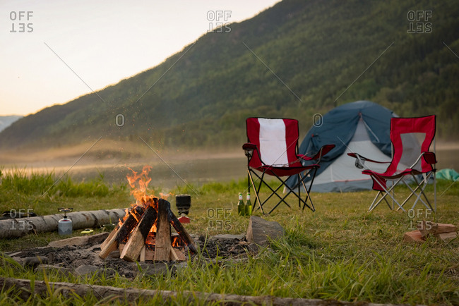 Empty camp chair with campfire at campsite