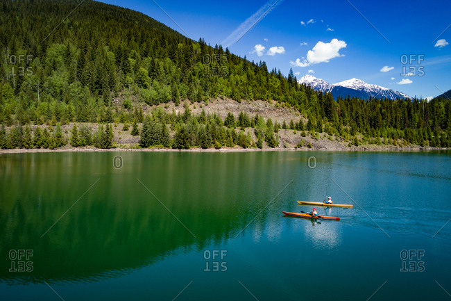 Distant view of couple kayaking in lake by mountain against sky