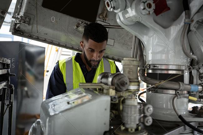 Male aircraft maintenance engineer examining turbine engine of an aircraft at airlines maintenance facility