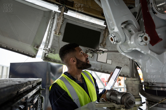 Male aircraft maintenance engineer examining engine of airplane at airlines maintenance facility