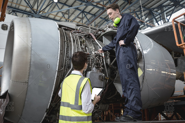 Male aircraft maintenance engineers examining turbine engine of aircraft at airlines maintenance facility
