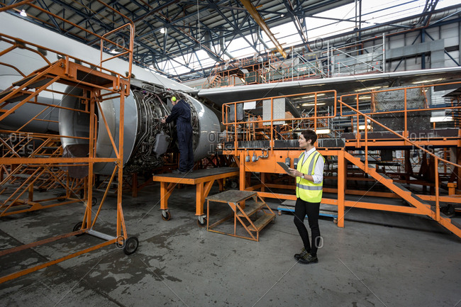 Male aircraft maintenance engineers examining turbine engine of aircraft at airlines maintenance facility