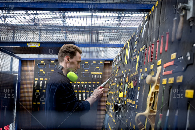 Male aircraft maintenance engineer examining various work tool at airlines maintenance facility