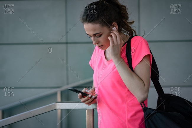 Fit woman using mobile phone outside fitness studio