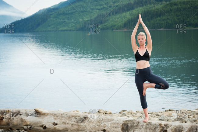 Young woman practicing tree pose on log against lake