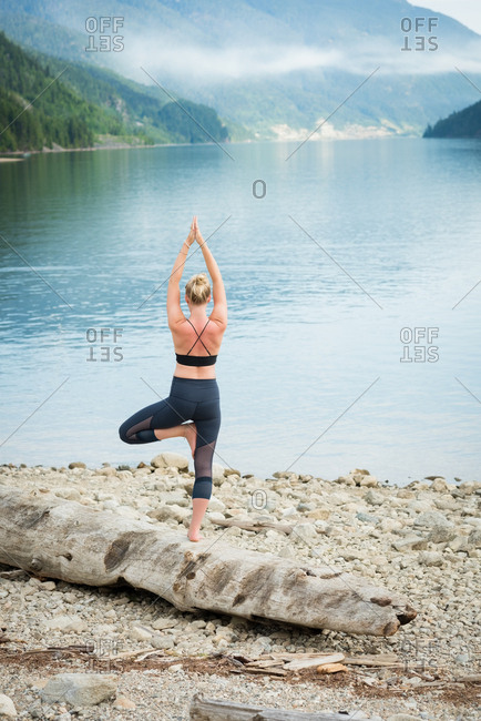 Rear view of woman practicing tree pose on log at lakeshore