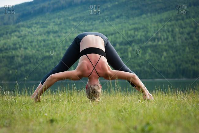 Woman practicing Prasarita Padottanasana on grass at lakeshore