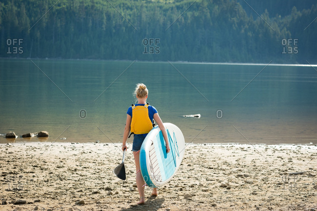 Rear view of woman carrying paddleboard and oar on lakeshore