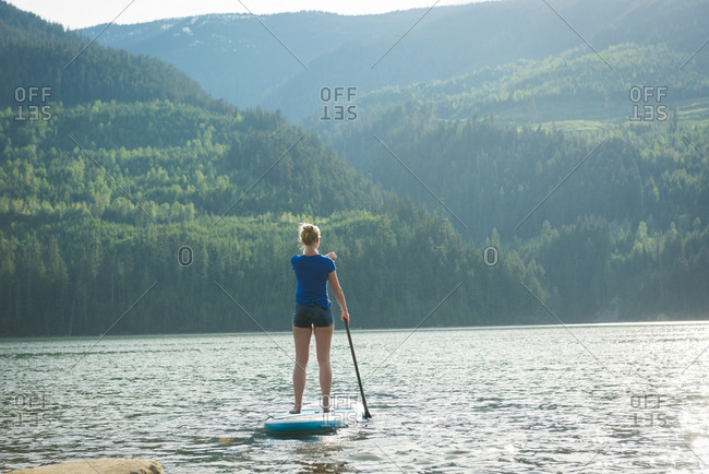 Rear view of woman paddleboarding in lake against mountains