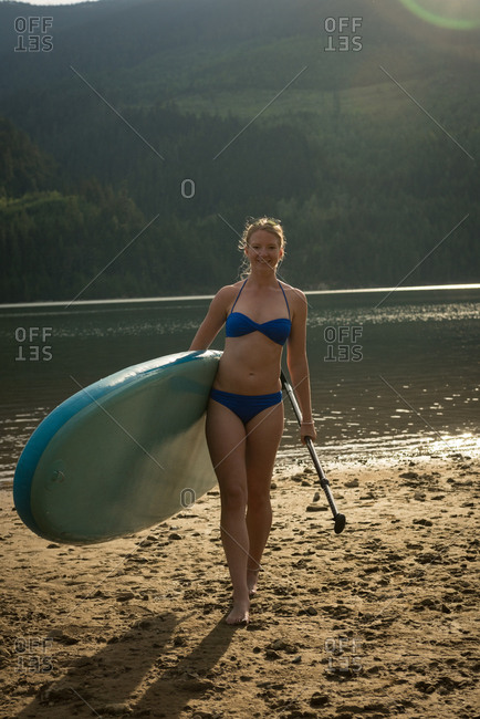 Portrait of smiling young woman carrying paddleboard and oar while walking on lakeshore