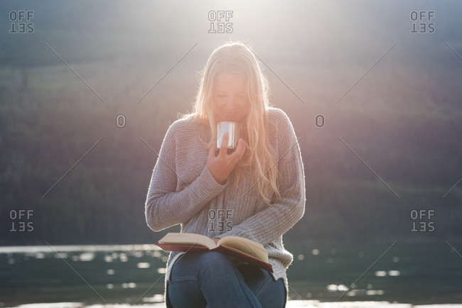 Young woman reading novel while having coffee against lake