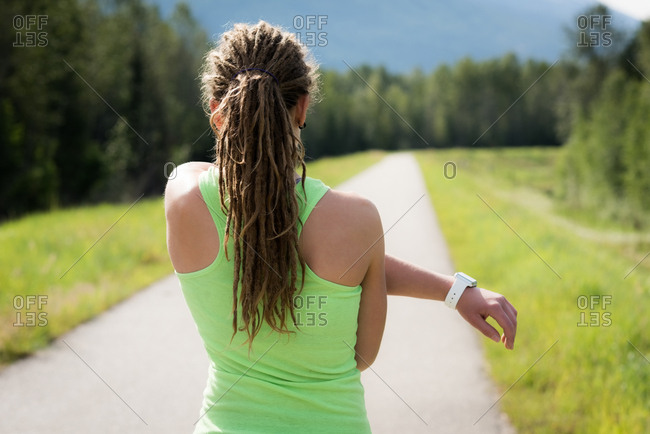 Rear view of woman with dreadlocks stretching on footpath against trees
