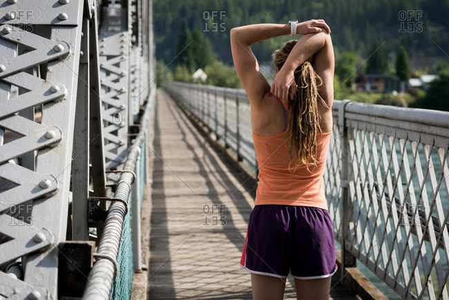 Rear view of woman stretching with arms raised on footbridge