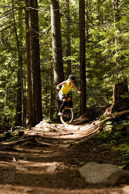 Woman unicycling on trail against trees in forest