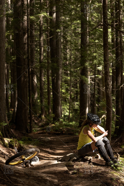 Woman sitting on rock by unicycle against trees in forest