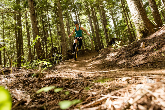 Surface level view of woman unicycling on trial against trees in forest