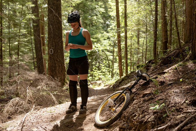 Woman using mobile phone while standing by unicycle on trail against trees