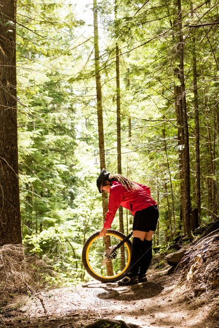 Woman adjusting unicycle while standing on trail against trees