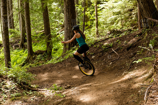 Rear view of woman unicycling on trial against trees in forest