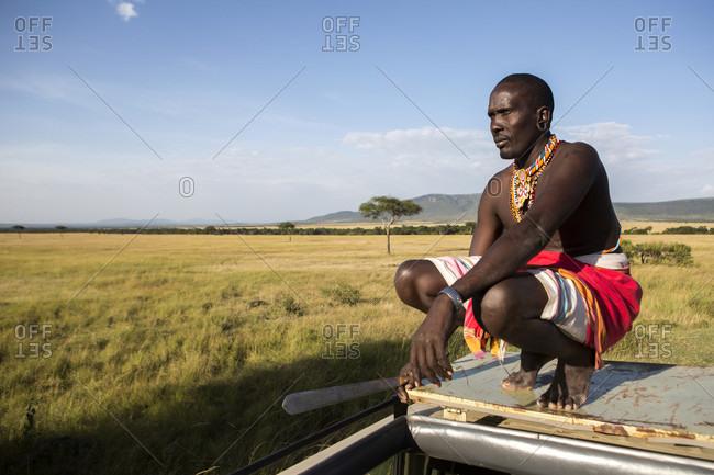 Masai Mara, Kenya - March 27, 2016: Samburu warrior sitting on a safari vehicle
