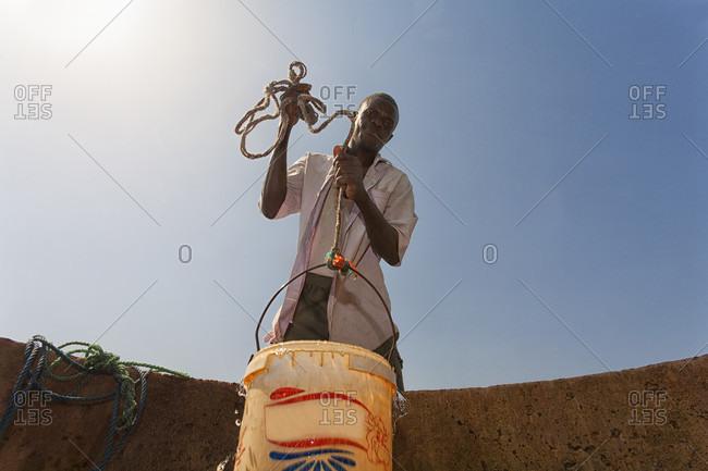 Sahel, Casamance, Senegal - May 29, 2015: Man fetching water from a well in the sahel region of the senegal river, senegal