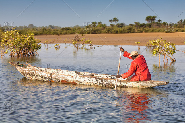 ziguinchor, casamance, senegal - February 1, 2007: Fisherman in his dugout canoe on the river casamance