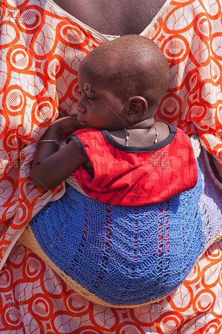ziguinchor, Casamance, Senegal - May 29, 2015: African bedik woman carrying a child while doing housework,  ziguinchor, casamance, senegal, africa