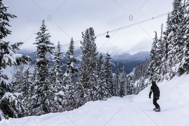 Whistler, British Columbia, Canada - December 6, 2015: Women snowboarding underneath peak 2 peak gondola at whistler blackcomb