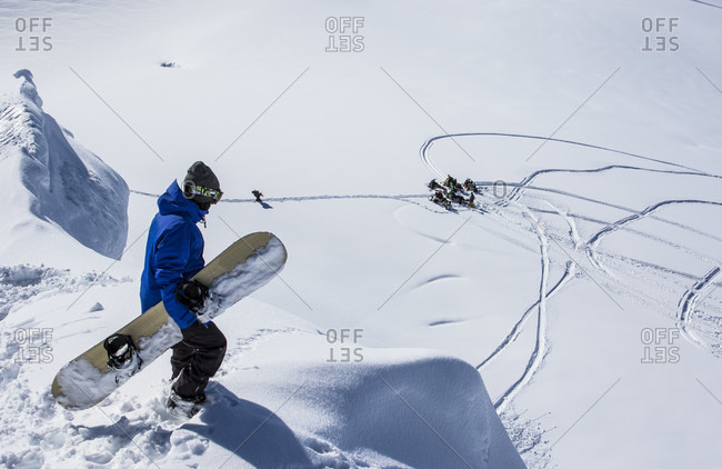 Haines Pass, British Columbia, Canada - April 4, 2015: A female snowboarder standing on top of her line before strapping in as her friends on snowmobiles watch from below