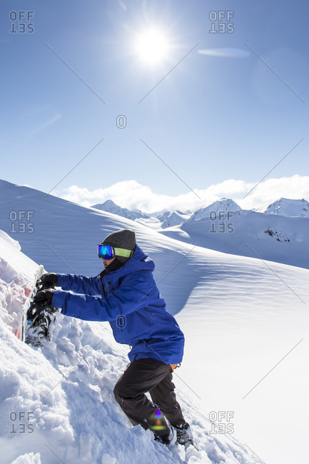 Haines Pass, British Columbia, Canada - April 4, 2015: A female snowboarder ascends snow mountain using snowboard