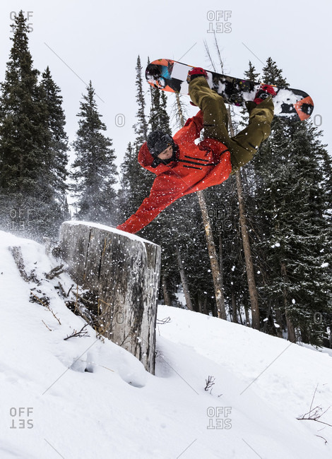 Brighton, Utah, USA - December 13, 2014: Snowboarder does a hand drag and gets inverted over a tree stump brighton resort, utah
