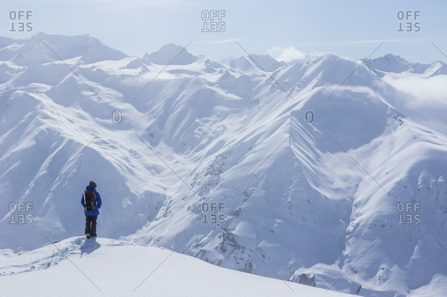 Haines Pass, British Columbia, Canada - April 5, 2015: A backcountry snowboarder standing on a ridgeline and overlooks distance mountains