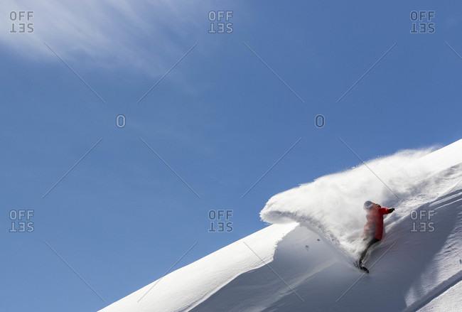 Silverton, Colorado, USA - March 8, 2015: Snowboarder performing slash and sprays powder snow in silverton, colorado, usa
